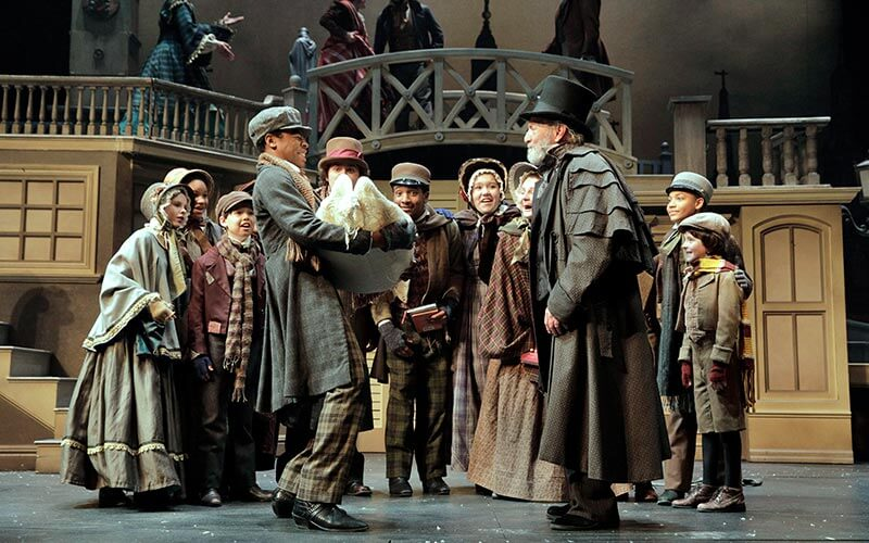 Actors performing on stage during a production of A Christmas Carol at the Kansas City Repertory Theatre in Kansas City, MO