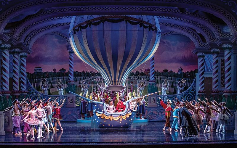 Actors from the Kansas City Ballet and Kansas City Symphony performing on stage with a hot air balloon prop during a production of The Nutcracker at the Kauffman Center for the Performing Arts in Kansas City, MO