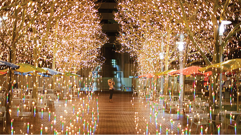 A woman taking photos of holiday lights at Crown Center in Kansas City, MO