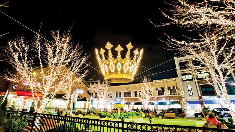 An oversized crown suspended above a grass square surrounded by lighted trees at Zona Rosa in Kansas City, MO
