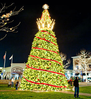 An oversized Christmas tree with a lighted crown at the top on display at Zona Rosa in Kansas City, MO