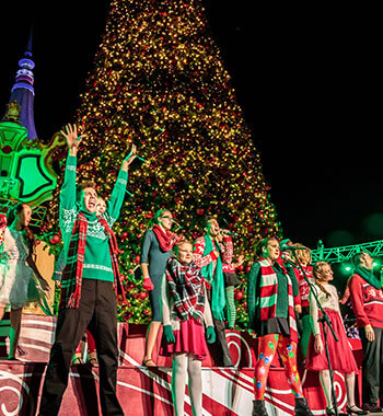 Performers dressed in holiday costumes on stage in front of an oversized Christmas tree at WinterFest at Worlds of Fun in Kansas City, MO