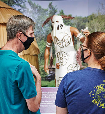 Two people wearing masks look at a Native American history exhibit at a museum in Kansas City, KS