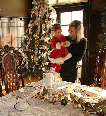 A mother standing in front of a Christmas tree holds her daughter to look at the dining table settings at the Wyeth-Tootle Mansion in St. Joseph, MO