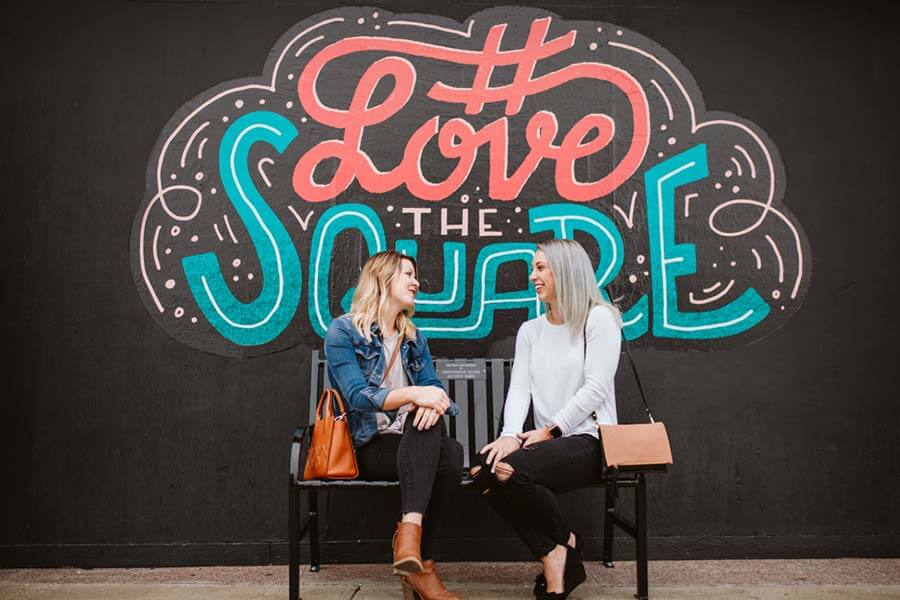 "Two women sitting on a bench in front of a mural that reads ""#LoveTheSquare"" near Historic Independence Square in Independence, MO"