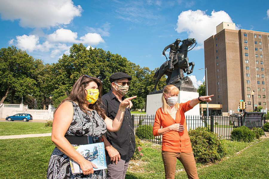 Three people wearing masks stand in front of the Pony Express Monument by Avard Fairbanks in St. Joseph, MO