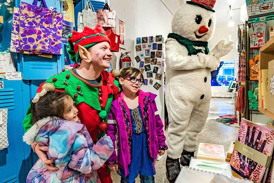 Two girls posing with a Christmas elf near a man in a snowman costume in St. Joseph, MO