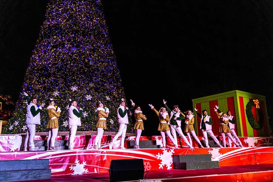 Performers singing in front of a 70-foot Christmas tree during the Cool Yule Christmas Show at WinterFest at Worlds of Fun in Kansas City, MO