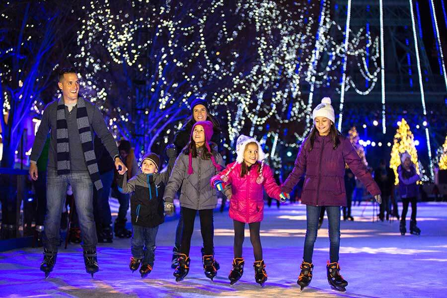 A family ice-skating on Snow Flake Lake at WinterFest at Worlds of Fun in Kansas City, MO