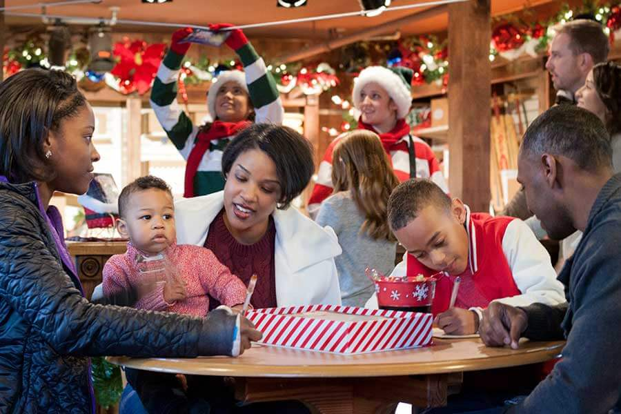 A family writing wish lists to Santa at WinterFest at Worlds of Fun in Kansas City, MO